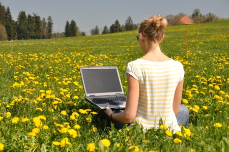 Girl with a laptop on the spring meadow photo