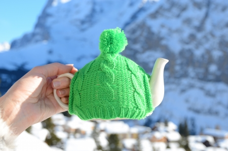 Tea pot in the knotted cap in the hand againstmountain scenery  photo