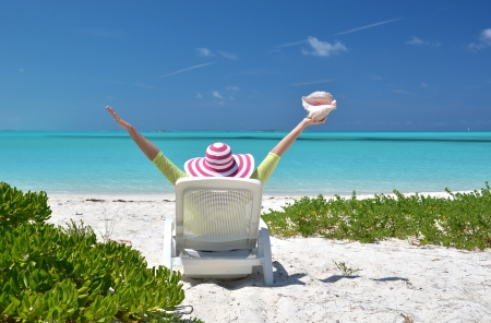 coolie hat: Girl with a shell on the sunbed looking to the ocean. Exuma, Bahamas Stock Photo