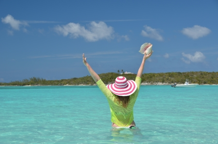 Girl with a seashell in the turqouise water of Atlantic. Exuma, Bahamas photo