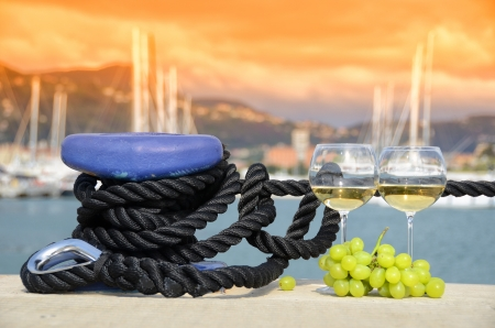 the mooring: Wineglasses and grapes on the yacht pier of La Spezia, Italy