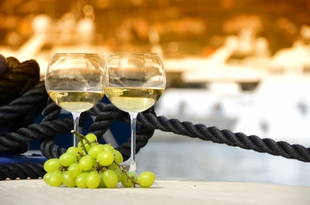 Wineglasses and grapes on the yacht pier of La Spezia, Italy  photo