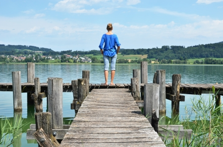 dream lake: Girl on the wooden jetty. Switzerland