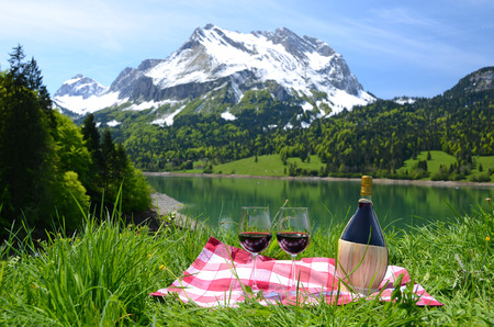 Wine and vegetables served at a picnic in Alpine meadow. Switzerland  Stock Photo