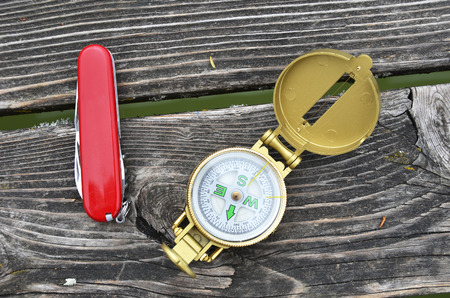 Compass and pocket knife on the wooden background photo