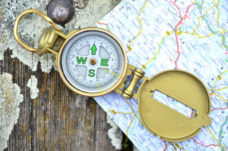 Compass and map on the wooden background photo