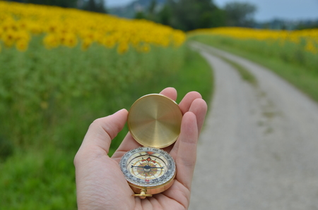 azimuth: Compass in the hand against rural road Stock Photo