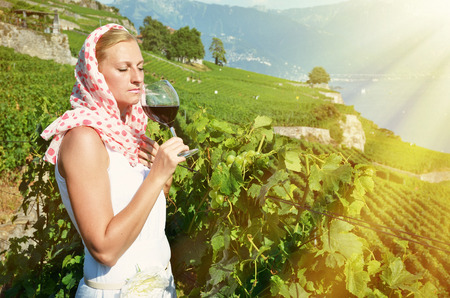 swiss culture: Girl tasting red wine in Lavaux, Switzerland