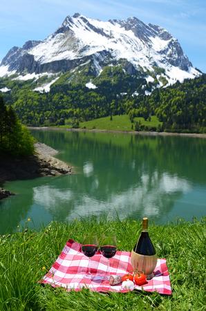 swiss alps: Wino i warzywa podawane na piknik na łące alpejskim. Szwajcaria