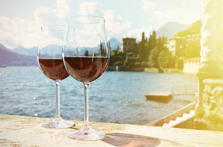Two wineglasses. Varenna town at the lake Como, Italy photo