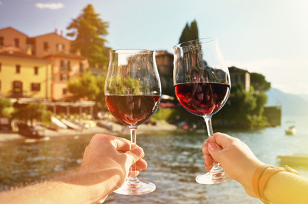 italian man: Two wineglasses in the hands. Varenna town at the lake Como, Italy