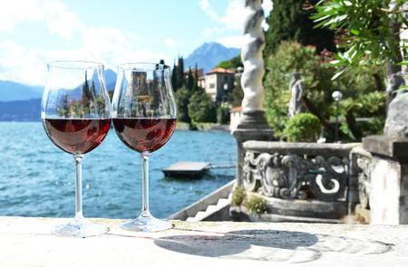 lake como: Two wineglasses. Varenna town at the lake Como, Italy Stock Photo