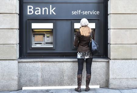 Meisje bij geldautomaat Stockfoto