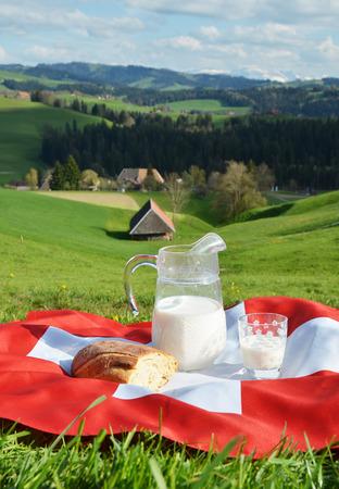 vacas lecheras: Jarro de leche en la bandera suiza. Emmental, Suiza Foto de archivo