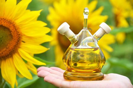 biofuel: Bottle of oil against sunflowers Stock Photo