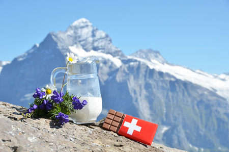 Zwitserse chocolade en kruik van melk tegen bergtop. Zwitserland