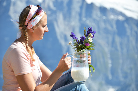 Girl holding a jug of milk and flowers against Swiss Alps photo