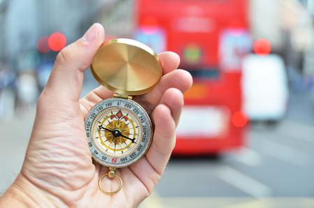 flèche double: Compass dans la main dans une rue de Londres