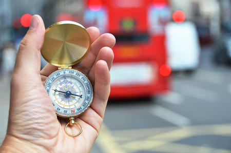 azimuth: Compass in the hand on a street of London