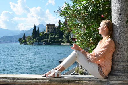 lake como: Girl with a wineglass at the Como lake, Italy