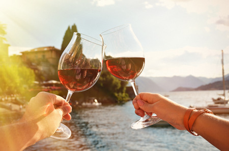 lake como: Two wineglasses in the hands. Varenna town at the lake Como, Italy