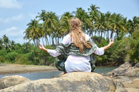 downshifting: Young woman meditating on Agonda beach. Goa, India