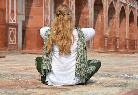 downshifting: Young woman meditating in the yard of Humayuns Tomb. Delhi, India Stock Photo