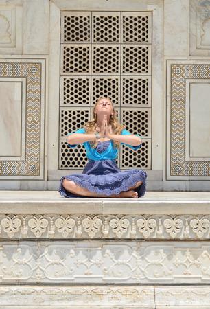 downshifting: Young woman meditating at the wall of Taj Mahal. Agra, India
