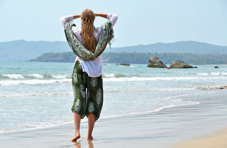 downshifting: Young woman in the traditional punjabi dress on Patnam beach. South Goa, India