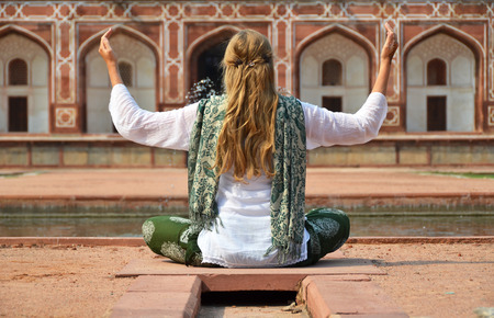 new delhi: Young woman meditating in the yard of Humayuns Tomb. Delhi, India Stock Photo