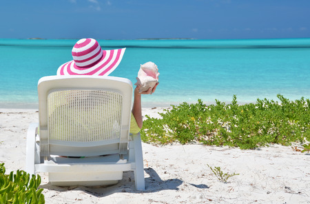 coolie hat: Girl in a striped hat on the beach of Exuma, Bahamas
