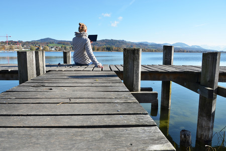 Girl reading from a tablet on the wooden jetty against a lake. Switzerland photo