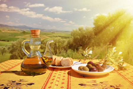 italy landscape: Olive oil, olives and bread on the wooden table against Tuscan landscape. Italy