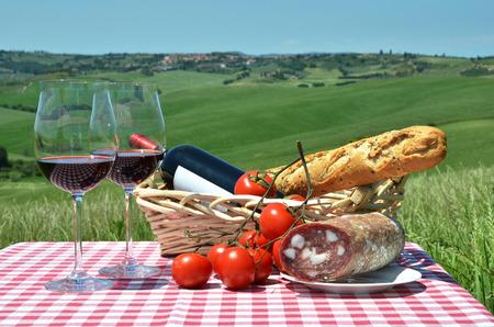 tomate de arbol: Rojo vino, pan y tomates en la tela a cuadros contra el paisaje de la Toscana. Italia Foto de archivo