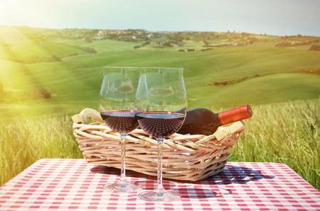 picnic cloth: Red wine on the chequered cloth against Tuscan landscape. Italy
