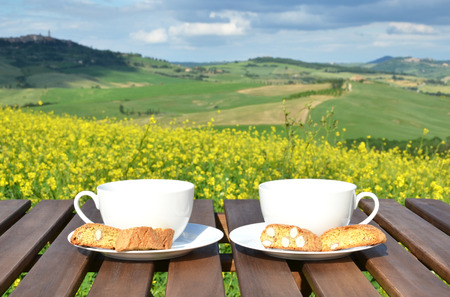 cups of coffee: Two coffee cups and cantuccini on the wooden table against Tuscan landscape, Italy