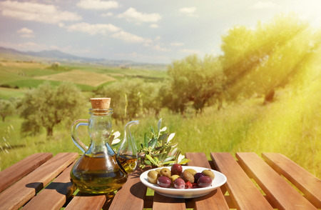 olive farm: Olive oil and olives and on the wooden table against Tuscan landscape. Italy