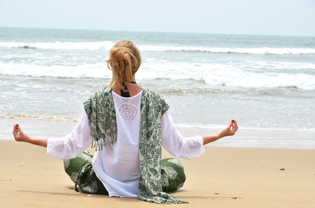 downshifting: Young woman in the traditional punjabi dress on Agonda beach. South Goa, India Stock Photo