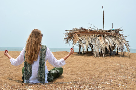 downshifting: Young woman meditating on Rajbag beach of South Goa. India