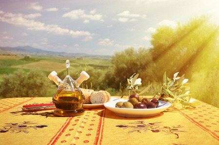 Olive oil, olives and bread on the table against Tuscan landscape. Italy