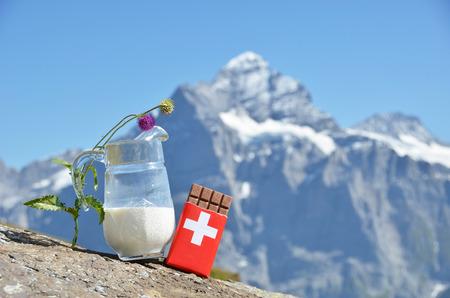 chocolate peak: Swiss chocolate and jug of milk against mountain peak. Switzerland