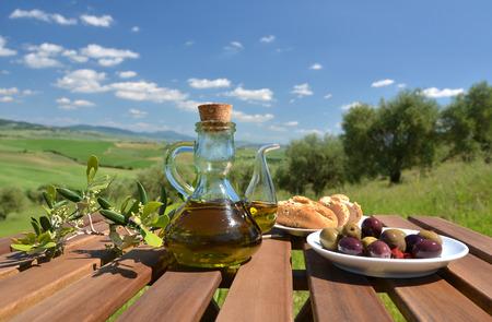 Olijfolie, olijven en brood op de houten tafel tegen Toscaans landschap. Italië