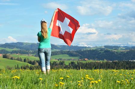 switzerland flag: Girl holding Swiss flag. Emmental, Switzerland