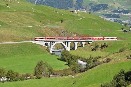 ancient pass: SWITZERLAND - SEP 16, 2012: Glacier Express of Matterhorn-Gotthard railway passing a bridge at Furka pass