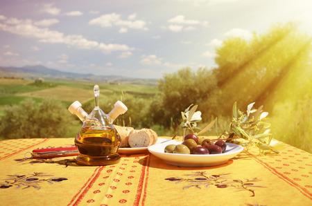 plato de comida: El aceite de oliva, aceitunas y pan en la mesa contra el paisaje de la Toscana. Italia