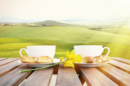 toscana: Coffee and cantuccini on the wooden table against Tuscan landscape. Italy