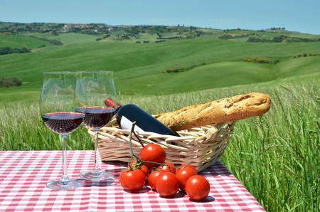 tomando vino: Rojo vino, pan y tomates en la tela a cuadros contra el paisaje de la Toscana. Italia Foto de archivo