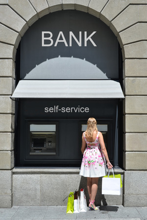 automatic teller machine bank: Girl with shopping bags at ATM