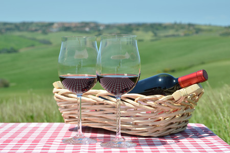 toscana: Red wine on the chequered cloth against Tuscan landscape. Italy