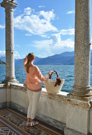 lake como: Girl with a basket bag at the Como lake, Italy Stock Photo